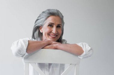 Happy grey haired woman looking at camera on chair isolated on grey stock vector