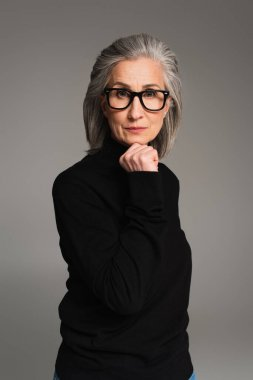 Mature woman in black jumper and eyeglasses looking at camera isolated on grey stock vector