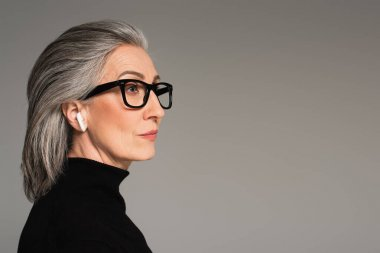 Mature woman in turtleneck, eyeglasses and earphone isolated on grey stock vector