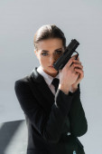 brunette woman holding handgun near face while looking at camera isolated on grey