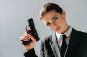 sensual, brunette woman looking at camera while holding handgun isolated on grey