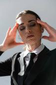 smyslná žena v síťovém závoji dotýkající se obličeje při pózování se zavřenýma očima izolovaných na šedé