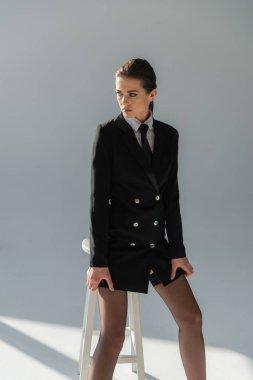 Trendy woman in black blazer dress looking away near high stool on grey background stock vector