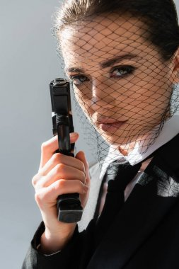 Sexy woman in net veil looking at camera while holding handgun isolated on grey stock vector