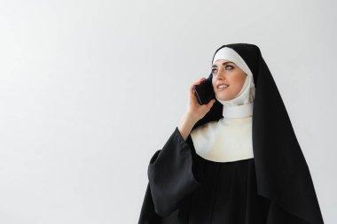 Joyful nun in black mantle talking on mobile phone isolated on grey stock vector