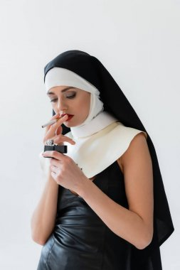 Young nun in leather dress lighting cigarette isolated on grey stock vector