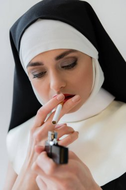 Young nun lighting cigarette isolated on grey, blurred foreground stock vector