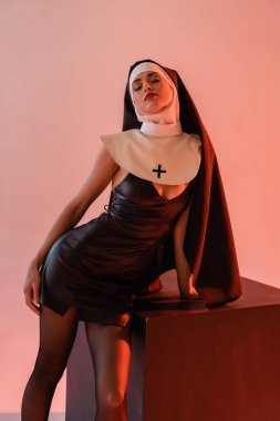 passionate nun in leather dress posing near black cube on pink background