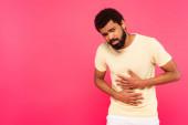 nespokojen africký Američan trpí bolestí žaludku izolované na růžové