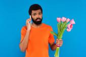 africký Američan drží růžové tulipány a mluví na smartphone izolované na modré