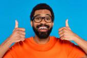 šťastný africký Američan v brýlích ukazující palce nahoru izolované na modré