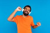 radostný africký Američan v bezdrátových sluchátkách poslech hudby izolované na modré