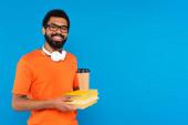 radostný africký Američan v bezdrátových sluchátkách drží knihy s papírovým kelímkem izolované na modré