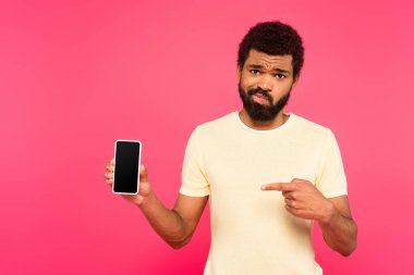 Confused african american man pointing at smartphone with blank screen isolated on pink stock vector