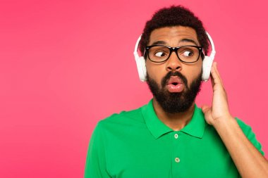 shocked african american man in glasses and wireless headphones isolated on pink