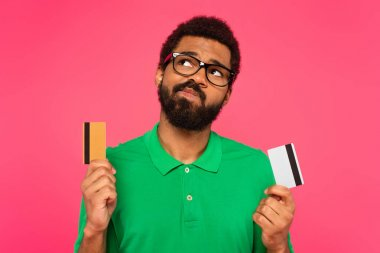 Confused african american man in glasses holding credit cards isolated on pink stock vector