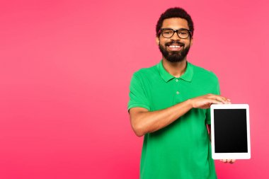 Happy african american man in glasses holding digital tablet with blank screen isolated on pink stock vector
