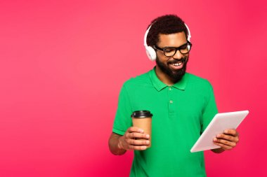 cheerful african american man in glasses and headphones holding paper cup and digital tablet on pink