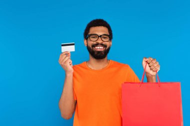 Happy african american man in glasses holding shopping bag and credit card isolated on blue stock vector