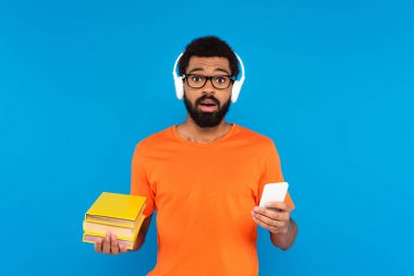 Confused african american man in wireless headphones holding books and smartphone isolated on blue stock vector
