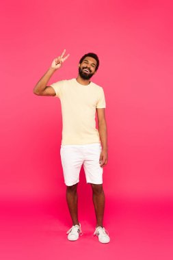 Full length of cheerful and bearded african american man showing peace sign on pink stock vector