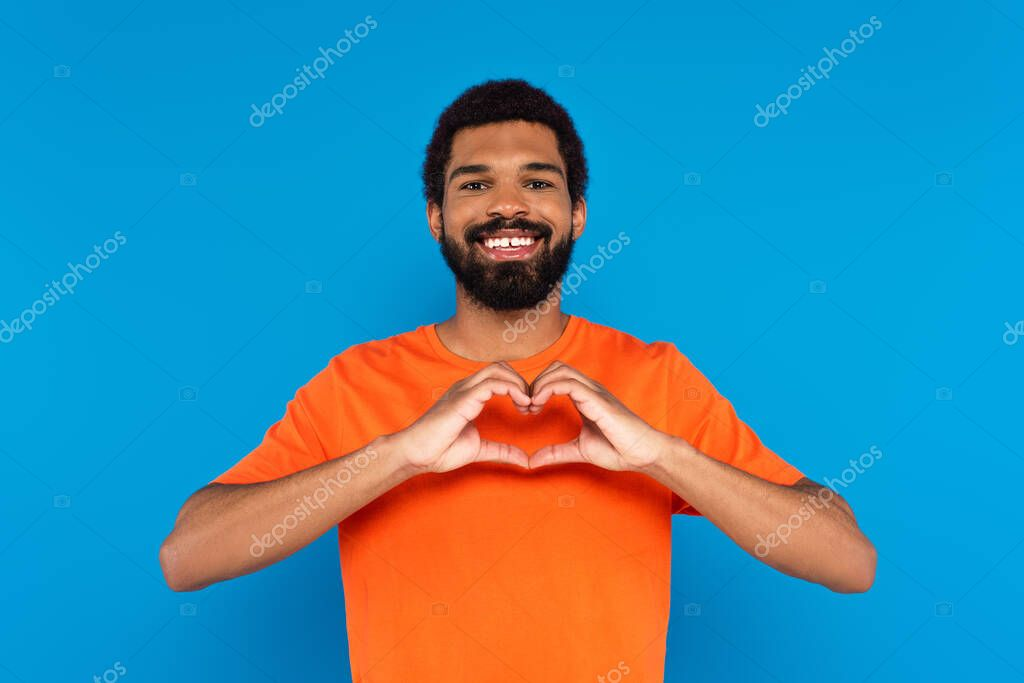 Happy and bearded african american man showing heart sign with hands isolated on blue stock vector