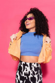 cheerful african american woman in sunglasses posing on pink