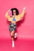 plná délka šťastný africký Američan žena v slunečních brýlích držení boombox a pózování na růžové