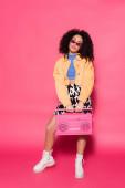 plná délka africké americké ženy drží retro boombox na růžové
