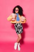 plná délka africké americké ženy ve slunečních brýlích drží vědra popcornu na růžové