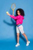 plná délka sportovní africké americké ženy držící tenisovou raketu a míč při hraní na modré