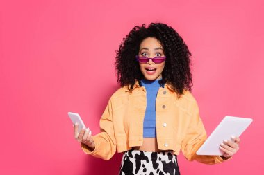 Confused african american woman in sunglasses holding smartphone and digital tablet on pink stock vector
