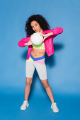 plná délka sportovní africké americké ženy v růžové bundě drží volejbal na modré