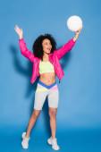 plná délka ohromený africký Američan žena v růžové bundě a plodiny top hrát volejbal na modré