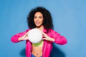 šťastná africká americká žena v růžové bundě a plodiny top hrát volejbal na modré
