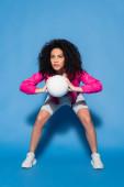 plná délka kudrnaté africké americké ženy v růžové bundě hrát volejbal na modré
