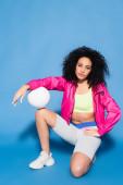 mladá africká americká žena v růžové bundě sedí s volejbalem na modré