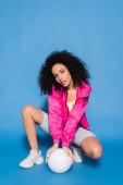 mladá africká americká žena v růžové bundě pózuje v blízkosti volejbal na modré