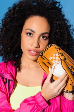 Curly african american woman in leather glove holding baseball isolated on blue stock vector