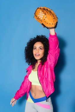 Sporty african american woman in leather glove playing baseball on blue stock vector