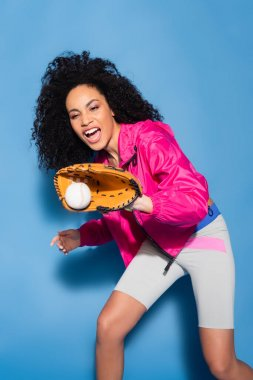 Excited african american woman in leather glove catching baseball on blue stock vector