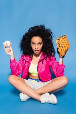 Curly african american woman in leather glove holding baseball while sitting with crossed legs on blue stock vector