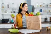 šťastná brunetka žena při pohledu na papírový sáček s čerstvými potravinami na kuchyňském stole