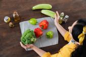 pohled shora bruneta žena v blízkosti čerstvé zeleniny na kuchyňském stole