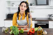 mladá bruneta žena drží nůž v blízkosti dřevěné sekání palubě a zeleniny na kuchyňském stole