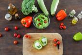 vrchní pohled na krájenou zelenou paprikou na dřevěné sekací desce v blízkosti zralé zeleniny