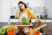 fáradt fiatal nő kötényben nézi zöldségek közelében serpenyő a konyhában