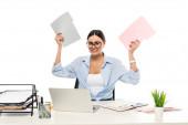 irritated businesswoman holding folders while sitting near laptop isolated on white