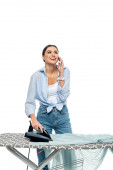 cheerful woman talking on mobile phone while ironing clothes isolated on white