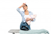 exhausted woman wiping forehead while holding newborn child near ironing board isolated on white
